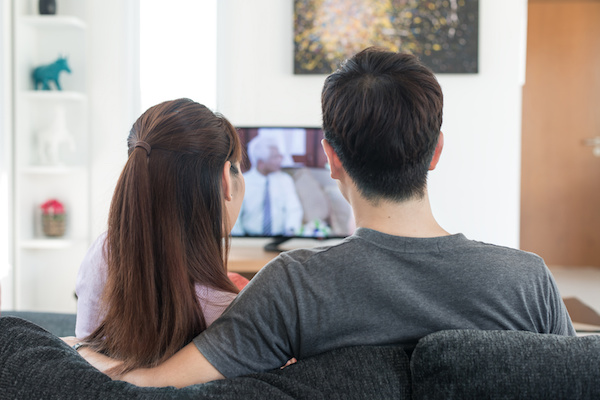 Young Asian couple waching movie on tv at home