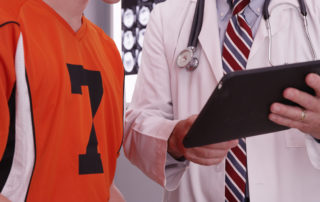 Portrait of medical doctor looking at tablet computer with college athlete.