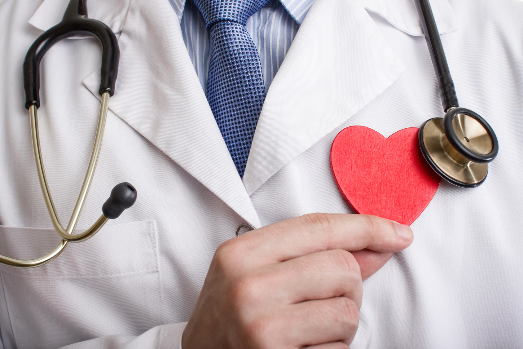 Doctor holding heart shape with stethoscope on his neck.