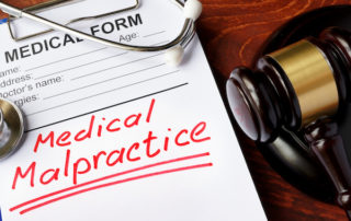 Medical form with words Medical Malpractice and gavel.